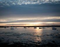 Puesta del sol sobre los barcos del oeste de la costa de la orilla del mar de essex del mersea del estuario del río fotografía de archivo