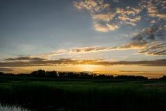 Puesta del sol sobre los campos Fotografía de archivo libre de regalías