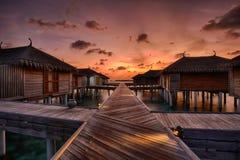 Puesta del sol sobre los chalets maldivos del agua Foto de archivo libre de regalías