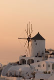 Puesta del sol sobre los molinoes de viento blancos en la ciudad de Oia y del panorama a la isla de Santorini, Thira, Grecia Foto de archivo libre de regalías