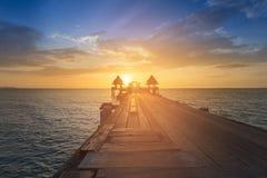 Puesta del sol sobre manera de madera del paseo con horizonte de la costa Foto de archivo libre de regalías