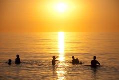 Puesta del sol sobre nadadores del océano Imagen de archivo libre de regalías