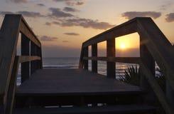 Puesta del sol sobre paseo marítimo por el mar Imágenes de archivo libres de regalías