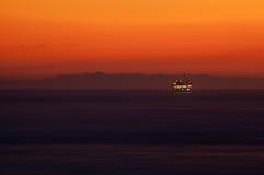 Puesta del sol sobre plataforma petrolera en el mar Fotografía de archivo