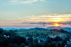 Puesta del sol sobre pueblo y las colinas verdes Foto de archivo libre de regalías