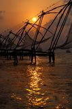 Puesta del sol sobre redes de pesca chinas en Cochin Fotos de archivo libres de regalías