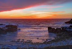 Puesta del sol sobre rocas y la arena en la playa de estado de Asilomar en California Imagen de archivo libre de regalías