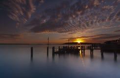 Puesta del sol sobre un embarcadero cerca de la isla de Brownsea en el puerto de Poole Foto de archivo