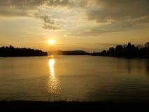 Puesta del sol sobre un lago Imagen de archivo
