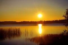 Puesta del sol sobre un lago Imagenes de archivo
