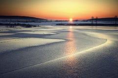 Puesta del sol sobre un lago congelado en la puesta del sol Fotografía de archivo libre de regalías