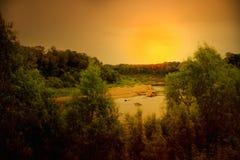 Puesta del sol sobre un río Fotos de archivo libres de regalías