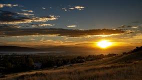 Puesta del sol sobre una ciudad en un valle con las montañas y un lago grande en la distancia foto de archivo