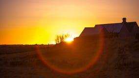 Puesta del sol sobre una granja Imagen de archivo libre de regalías