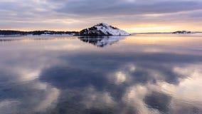 Puesta del sol sueca y la reflexión agradable de la isla en un océano Vaya foto de archivo