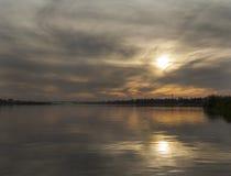 Puesta del sol tempestuosa sobre el río Imágenes de archivo libres de regalías