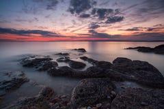 Puesta del sol tranquila en la costa costa rugosa Fotografía de archivo libre de regalías