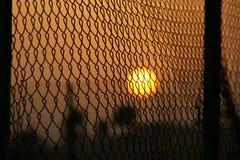 Puesta del sol a través de la frontera Foto de archivo