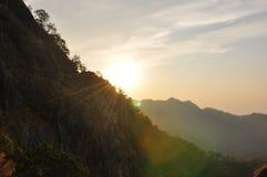 Puesta del sol a través de la montaña Fotos de archivo libres de regalías