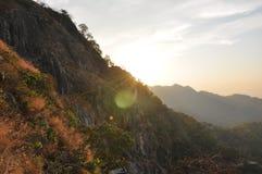 Puesta del sol a través de las montañas Foto de archivo libre de regalías