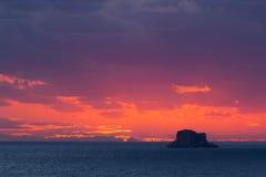Puesta del sol a través de las nubes con Filfla en el primero plano Imagen de archivo