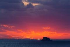 Puesta del sol a través de las nubes con Filfla en el primero plano Fotografía de archivo libre de regalías