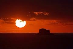 Puesta del sol a través de las nubes con Filfla en el primero plano Foto de archivo libre de regalías