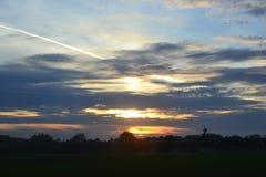 Puesta del sol a través de las nubes sobre campo Imagen de archivo libre de regalías