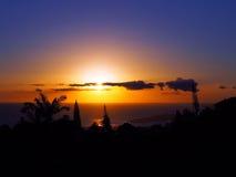 Puesta del sol a través de las nubes sobre el Océano Pacífico con el refl ligero Imagen de archivo libre de regalías