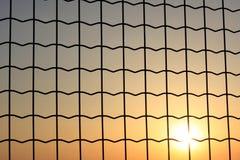 Puesta del sol a través de un acoplamiento de alambre Foto de archivo