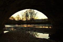 Puesta del sol a través del arco Foto de archivo libre de regalías