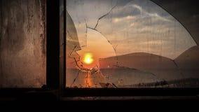 puesta del sol a través del vidrio quebrado Fotografía de archivo libre de regalías