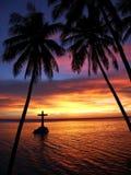 Puesta del sol tropical con la silueta de la cruz y de los árboles Fotografía de archivo