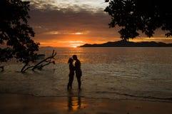Puesta del sol tropical, orilla del océano con la silueta de un par del amante Foto de archivo libre de regalías
