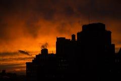 Puesta del sol urbana dramática en la silueta de New York City Imagen de archivo libre de regalías