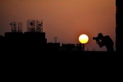 Puesta del sol urbana y el fotógrafo Imagenes de archivo
