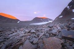 Puesta del sol vibrante tranquila con la coloración roja insana de las montañas del valle del glaciar foto de archivo