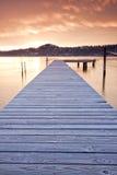 Puesta del sol vista de un muelle en un lago mountain Foto de archivo libre de regalías