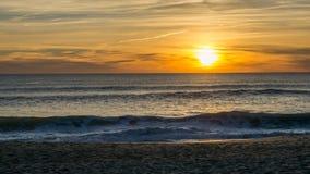Puesta del sol viva hermosa de la playa en Faro, Algarve, Portugal imagen de archivo