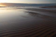 Puesta del sol viva roja en el mar Báltico con el espejo como el agua - arena y ondas acanaladas - Veczemju Klintis, Letonia - 1 imagen de archivo