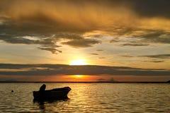 Puesta del sol y barco del mar. Imagen de archivo libre de regalías