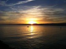Puesta del sol y barco solo Imagen de archivo libre de regalías