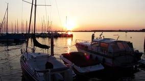 Puesta del sol y barcos en el puerto metrajes
