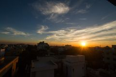 Puesta del sol y ciudad imagen de archivo