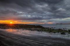 Puesta del sol y costa rocosa áspera Imagenes de archivo