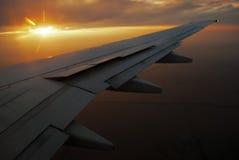 Puesta del sol y el ala del aeroplano Imagen de archivo libre de regalías