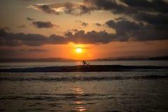 Puesta del sol y el practicar surf Fotografía de archivo