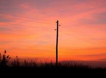 Puesta del sol y electricidad rojas Fotos de archivo libres de regalías