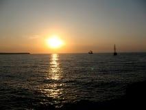 Puesta del sol y naves en el mar Imagen de archivo libre de regalías