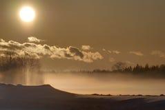 Puesta del sol y niebla del invierno Fotos de archivo
